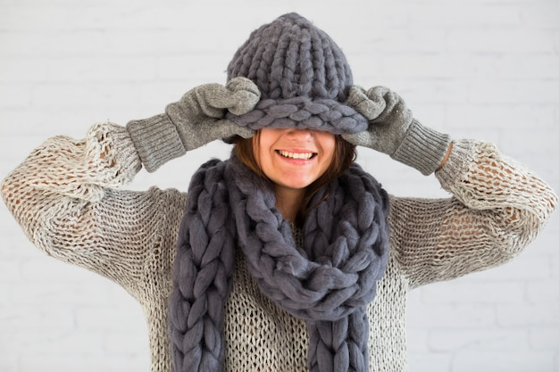 Smiling lady in mittens, scarf and hat on eyes Free Photo