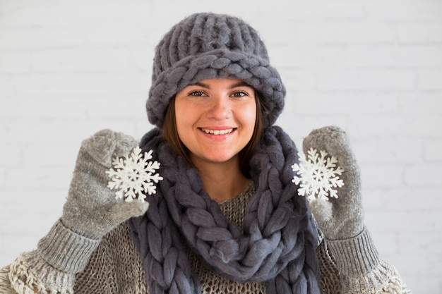 Smiling lady in mittens, scarf and hat with ornament snowflakes in hands Free Photo
