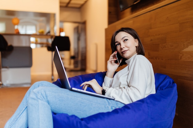 クリエイティブ・オフィスのバッグの椅子に携帯電話とラップトップを使用して笑顔の女性 無料写真
