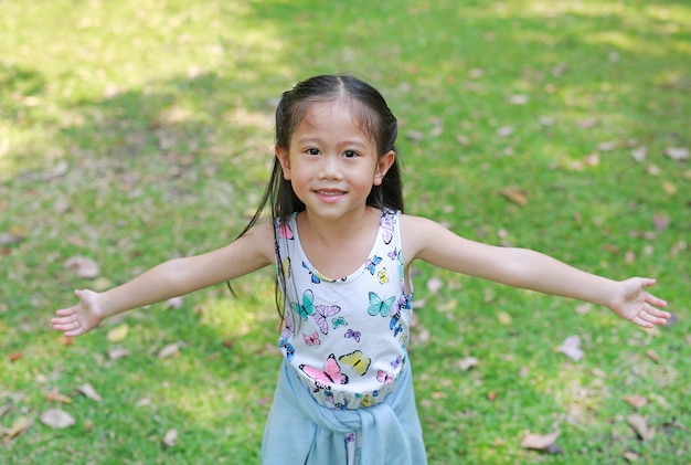 Smiling little asian child girl opened her hands in the summer garden. Premium Photo