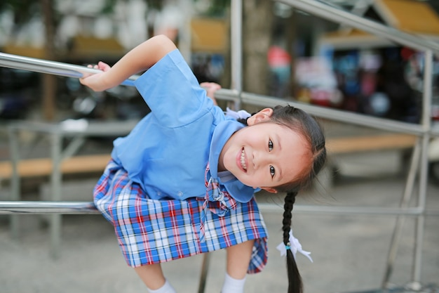 c53f5a89710b Smiling little asian girl in school uniform playful hanging at metal  railing. Premium Photo