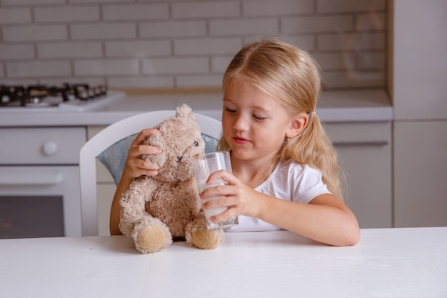 Smiling little blonde girl drinking milk in the kitchen Premium Photo