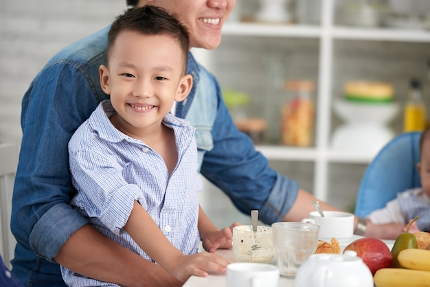 Smiling little boy at breakfast with family Free Photo