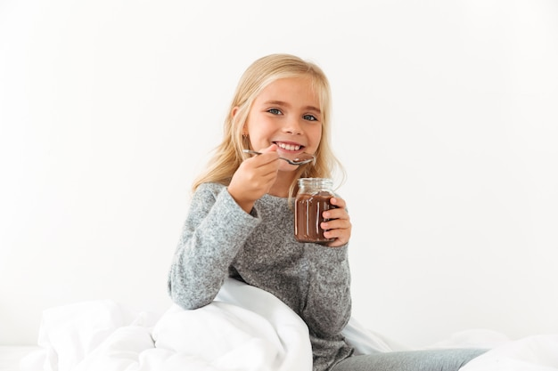 Smiling little girl holding bank of sweet chocolate hazelnut spread,  while sitting in bed Free Photo