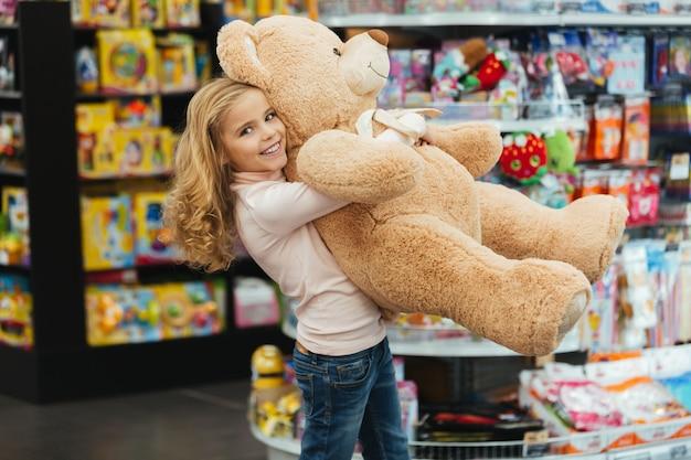 Smiling little girl holding big teddy bear Free Photo