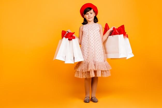 ショッピングバッグを持って笑顔の少女。黄色の壁に立っているドレスを着た陽気な子供。 無料写真