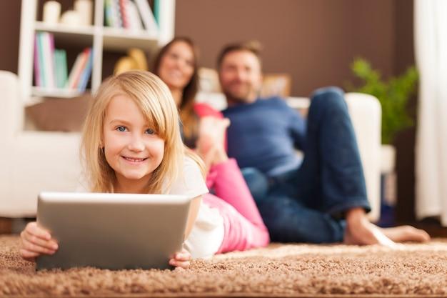 Bambina sorridente che gioca sul tablet e sdraiato sul tappeto Foto Gratuite