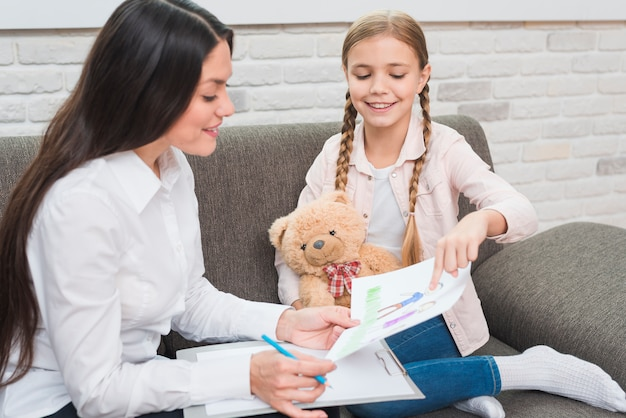 Smiling little girl showing drawn drawing paper to the female psychologist Free Photo