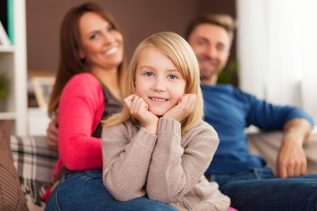Bambina sorridente con i genitori a casa Foto Gratuite