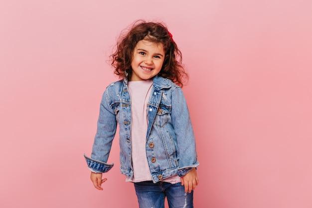 Улыбающаяся маленькая девочка с волнистыми волосами, стоя на розовом фоне. студия выстрел очаровательного подросткового ребенка носить джинсовую куртку. Бесплатные Фотографии