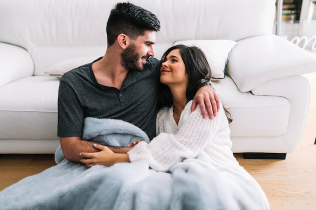 Smiling loving couple sitting in one blanket at living room Free Photo