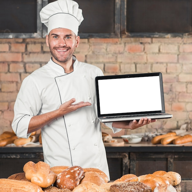 Smiling male baker standing in front of table with different type of breads Free Photo