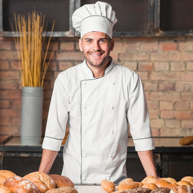 Smiling male baker with freshly baked breads Free Photo