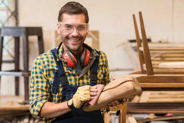 Smiling male carpenter smoothing wooden structure with sand paper Free Photo