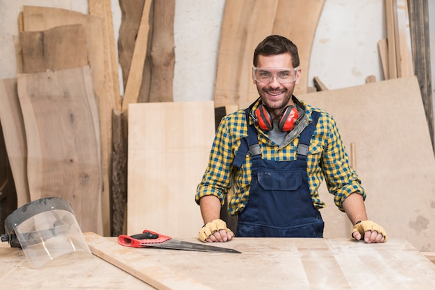 Smiling male carpenter standing behind the workbench Free Photo