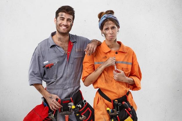 笑顔の男性大工が、動揺して疲れた女性同僚を励ます 無料写真