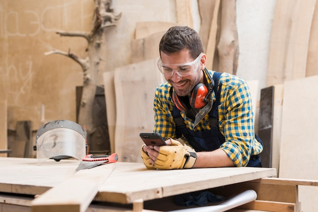 Smiling male carpenter wearing safety glasses and ear defender around his neck using cellphone Free Photo