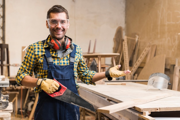 Smiling male carpenter wearing safety glasses holding handsaw gesturing Free Photo
