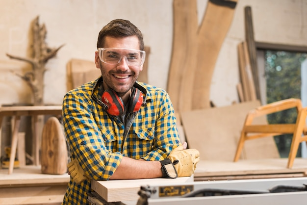 Smiling male carpenter with ear defender around her neck standing in his workshop Free Photo