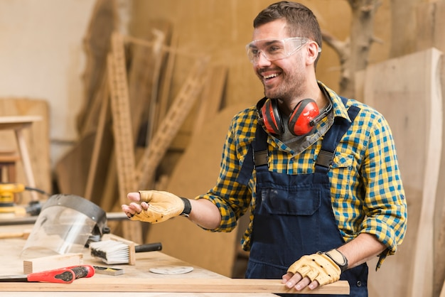 Smiling male carpenter at work in the workshop Free Photo