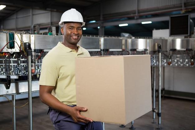 ジュース工場で段ボール箱を運ぶ男性従業員の笑顔 無料写真