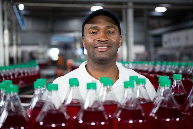 工場でジュース瓶のそばに立っている男性従業員の笑顔 無料写真