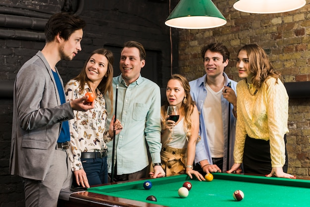 Smiling male and female friends looking at man holding snooker ball in club Free Photo