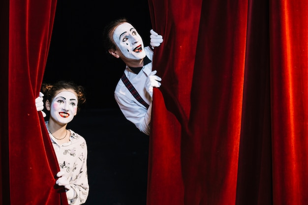 Smiling male and female mime artist peeking from red curtain Premium Photo