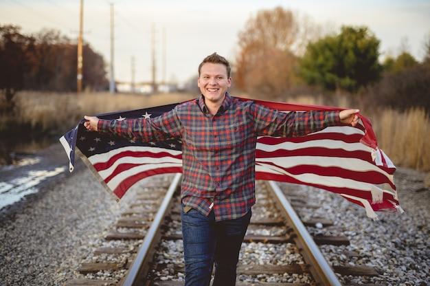 Maschio sorridente che tiene la bandiera degli stati uniti mentre si cammina sui binari del treno Foto Gratuite