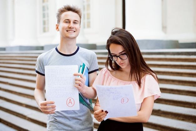 Smiling male and sad female with examination results near the university Premium Photo