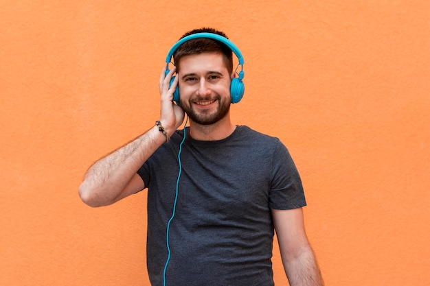 Smiling male with blue headphones Free Photo