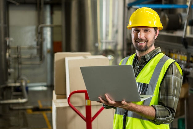 Smiling male worker using laptop in distribution warehouse Free Photo