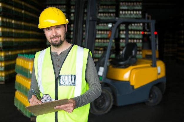 倉庫のクリップボードに書いている笑顔の男性労働者 無料写真