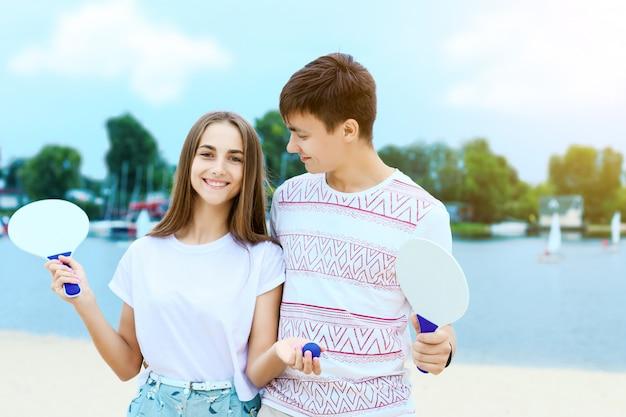 웃는 남자와 여자는 포옹과 라켓을 잡고있다. 프리미엄 사진