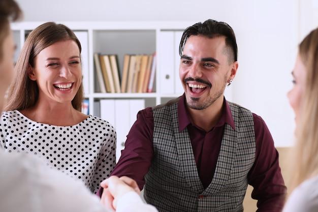 Улыбающиеся мужчина и женщина пожимают друг другу руки в офисе Premium Фотографии