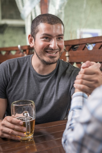 Smiling man arm wrestling with friend in bar Free Photo