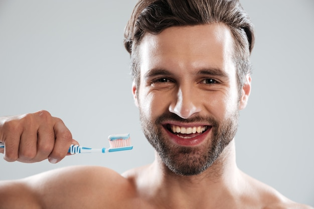 Smiling man brushing teeth Free Photo