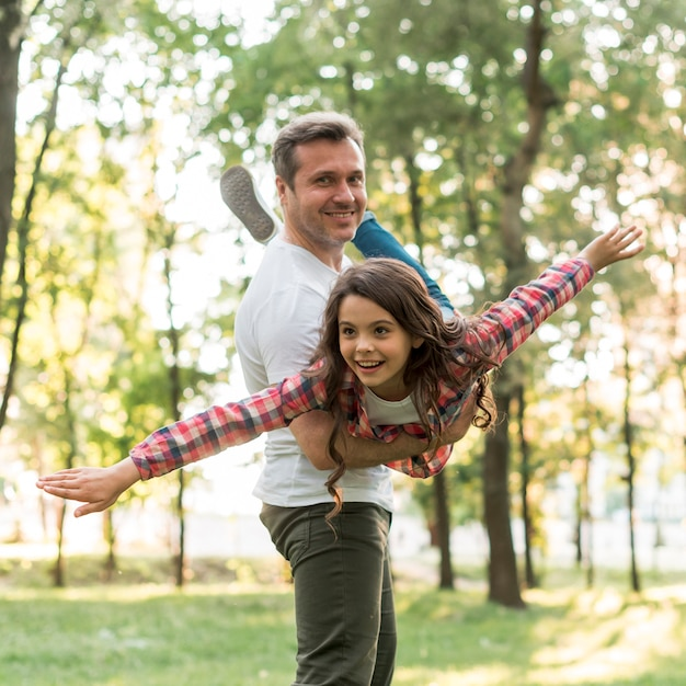Smiling man carrying his cute daughter in park Free Photo