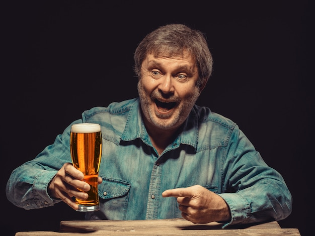 The smiling man in denim shirt with glass of beer Free Photo