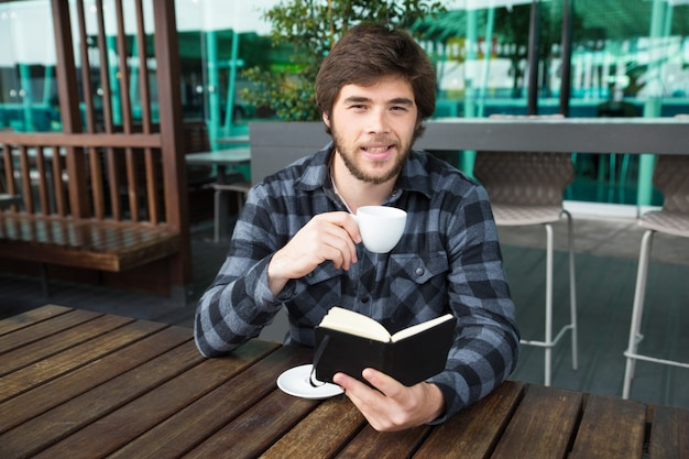 Smiling man drinking coffee and reading diary in street cafe Free Photo
