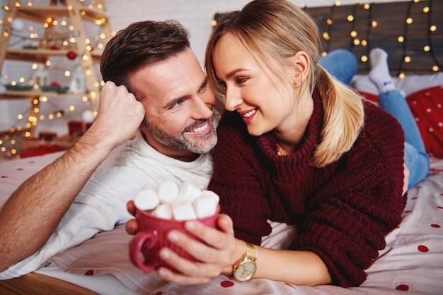 クリスマスに彼のガールフレンドを抱きしめる笑顔の男 無料写真