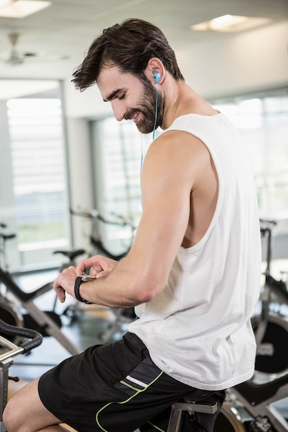 Smiling man on exercise bike using smartwatch at the gym Premium Photo