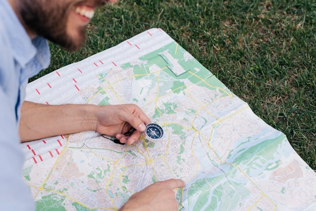 Smiling man holding compass and pointing at map on grass Free Photo
