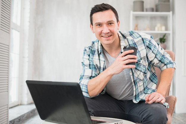 Smiling man holding cup of beverage on chair near laptop at home Free Photo