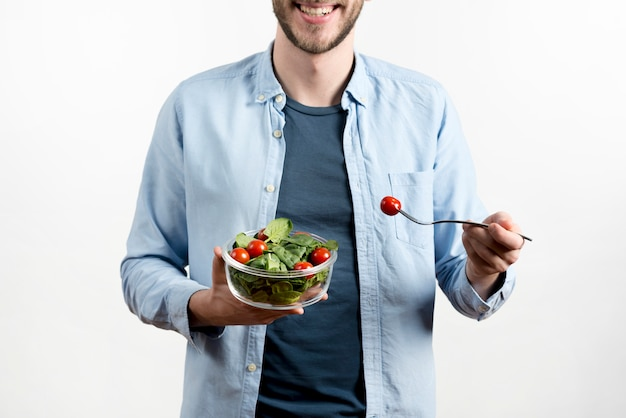 Smiling man holding fork with cherry tomato bowl salad against white background 23 2148076227