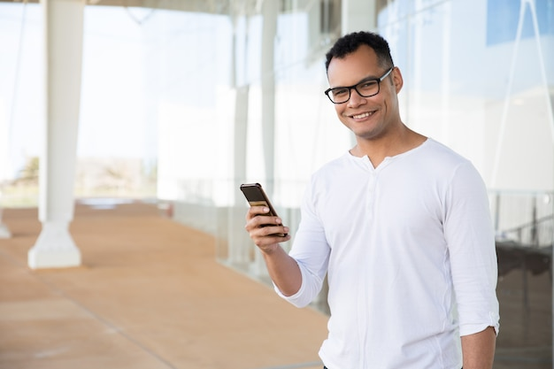 Smiling man holding phone in hands, turning head to camera Free Photo