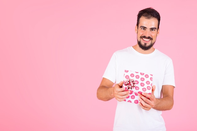 Smiling man holding pink floral gift box against pink backdrop Free Photo