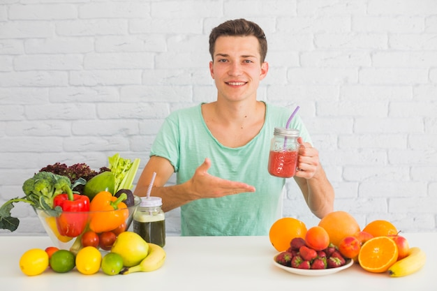 Smiling man holding red smoothie jar offering fresh healthy food Free Photo