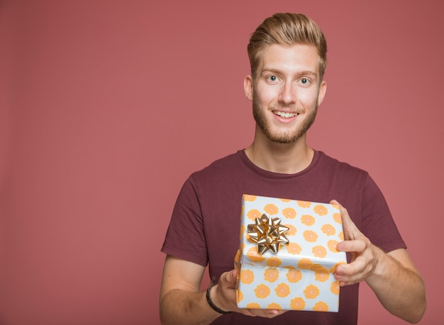 Smiling man holding wrapped gift box against colored background Free Photo