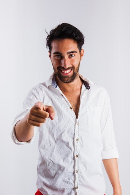 Smiling man in summer wear making pointing gesture Free Photo